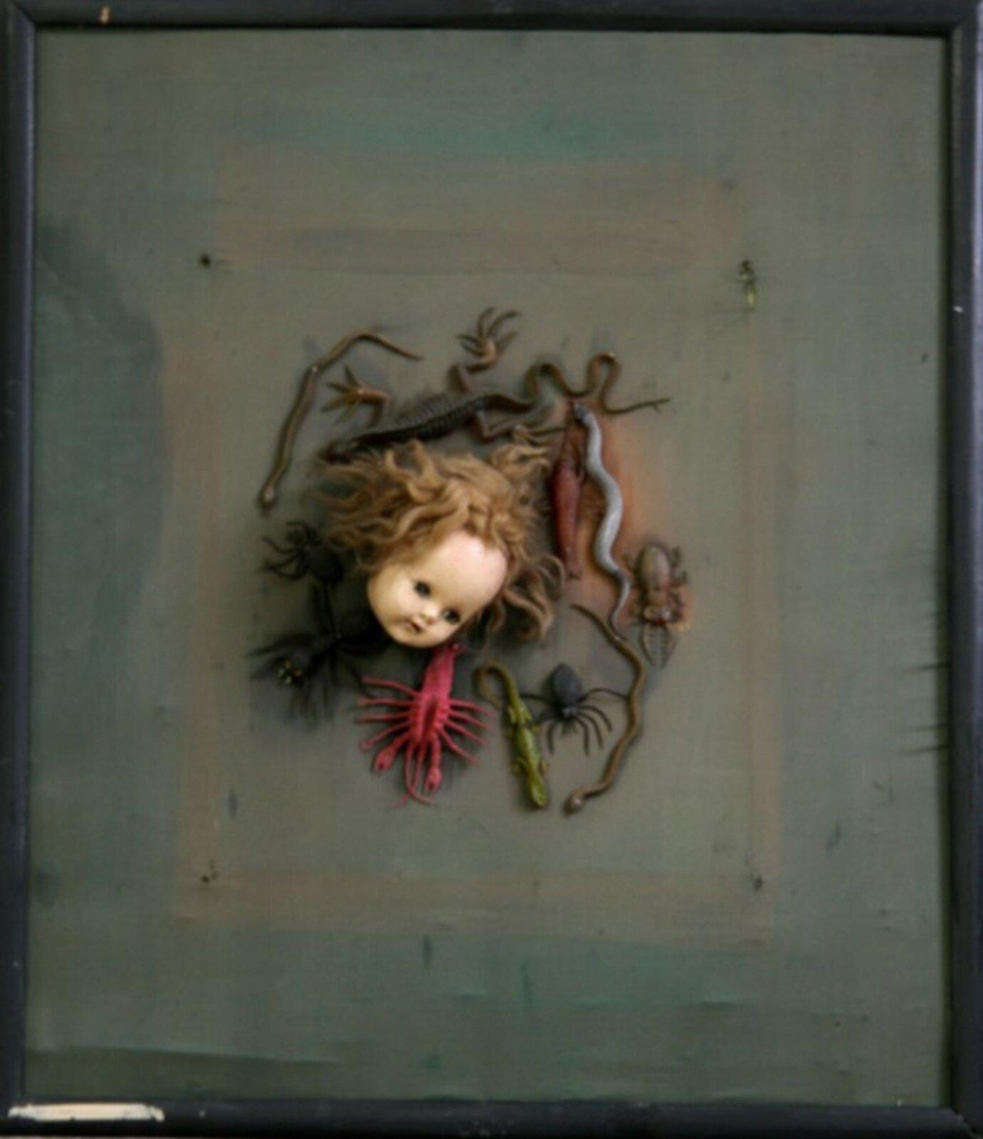 """Ilustracja przedstawiająca asamblaż Władysława Hasiora pt. """"Zielona rozpacz"""". Przedstawia on głowę lalki wokół, której znajdują się figurki gadów iowadów."""