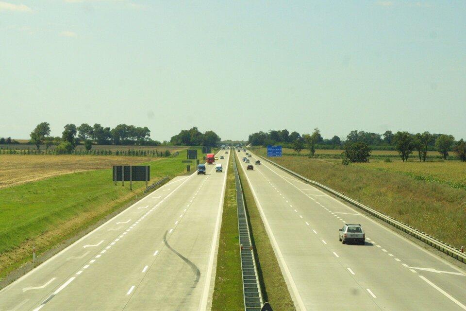 Na zdjęciu autostrada, dwa pasy ipobocze wkażdym kierunku. Po obu stronach pola uprawne.