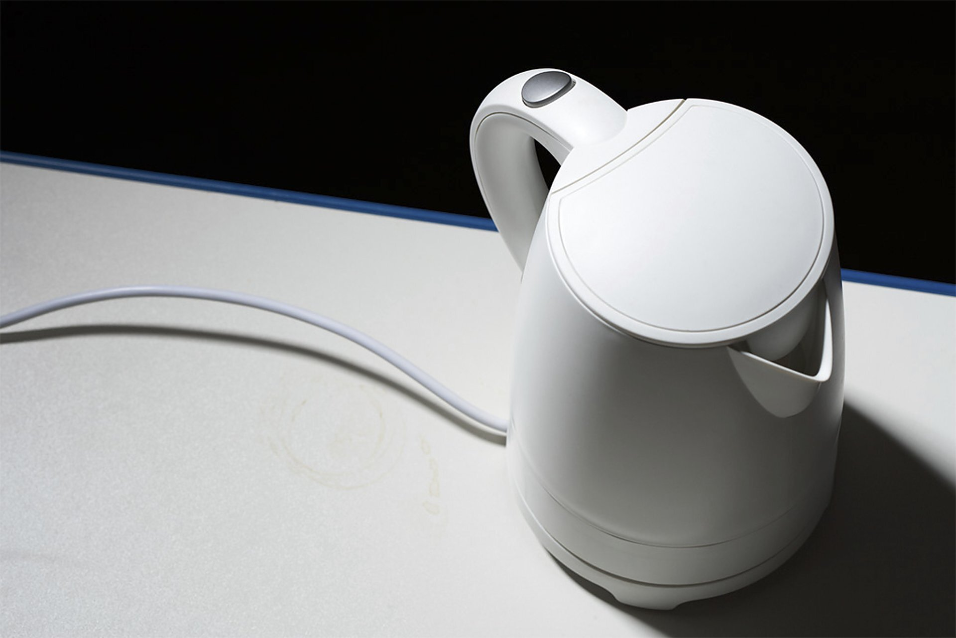 Zdjęcie przedstawia biały czajnik elektryczny stojący na białym blacie kuchennym uchwycony od góry. Czajnik stoi zprawej strony kadru, aoświetlony jest zlewej strony. Tło za blatem czarne.
