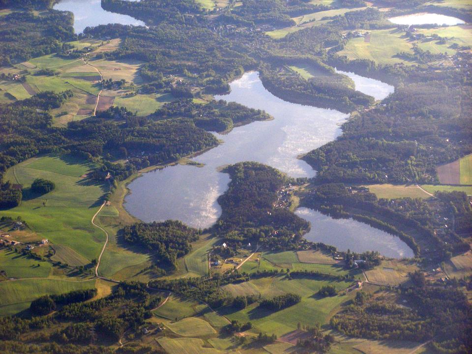 Drugie zdjęcie wykonane zlotu ptaka, przedstawia liczne jeziora Kaszub, umiejscowione pomiędzy polami ilasami