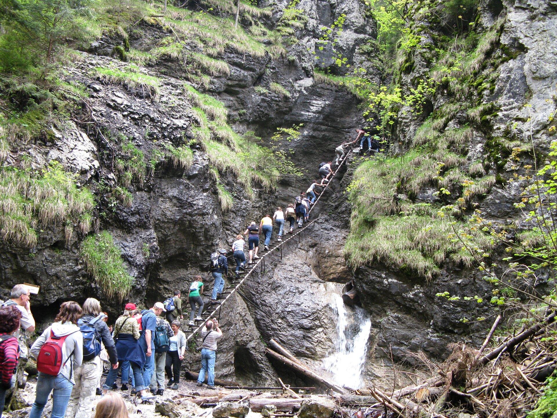 Na zdjęciu stromy, skalisty stok górski, po metalowych schodach wchodzą turyści. Ustóp wzniesienia kolejka.