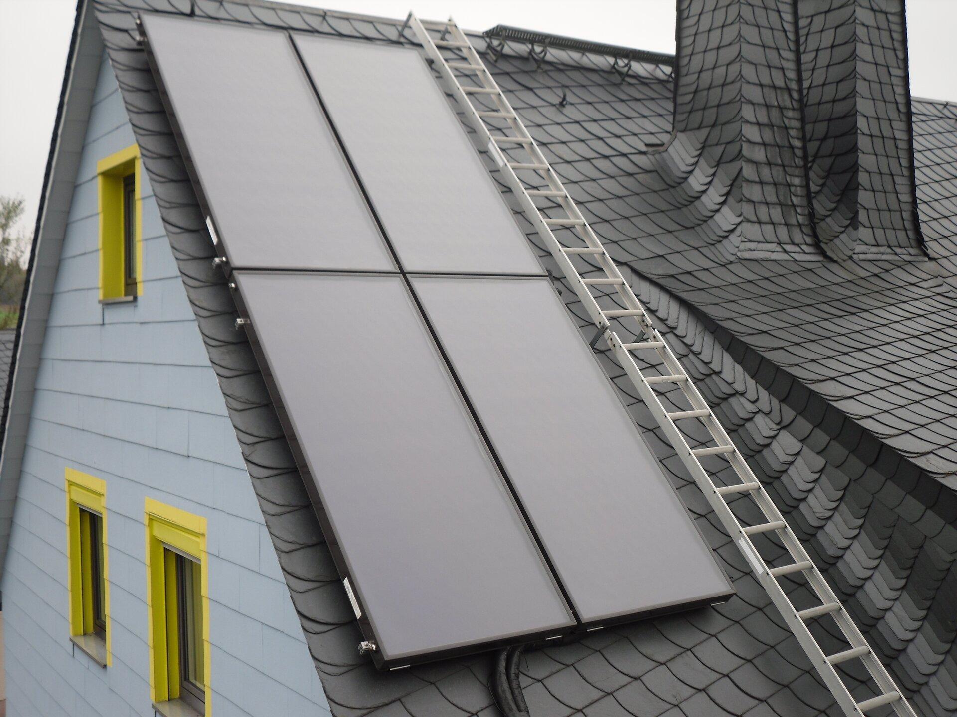 Na zdjęciu cztery płaskie kolektory słoneczne na dachu budynku. Obok kolektorów drabinka.