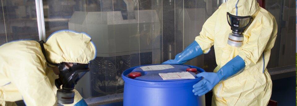 Kolorowe zdjęcie przedstawiające dwie osoby ubrane wżółte kombinezony ochronne idługie niebieskie rękawice. Osoby znajdują się wzamkniętym, przeszklonym pomieszczeniu, mają założone maski przeciwgazowe. Jedna zosób ma oparte ręce na dużej, niebieskiej beczce. Obie osoby mają głowy pochylone wdół.