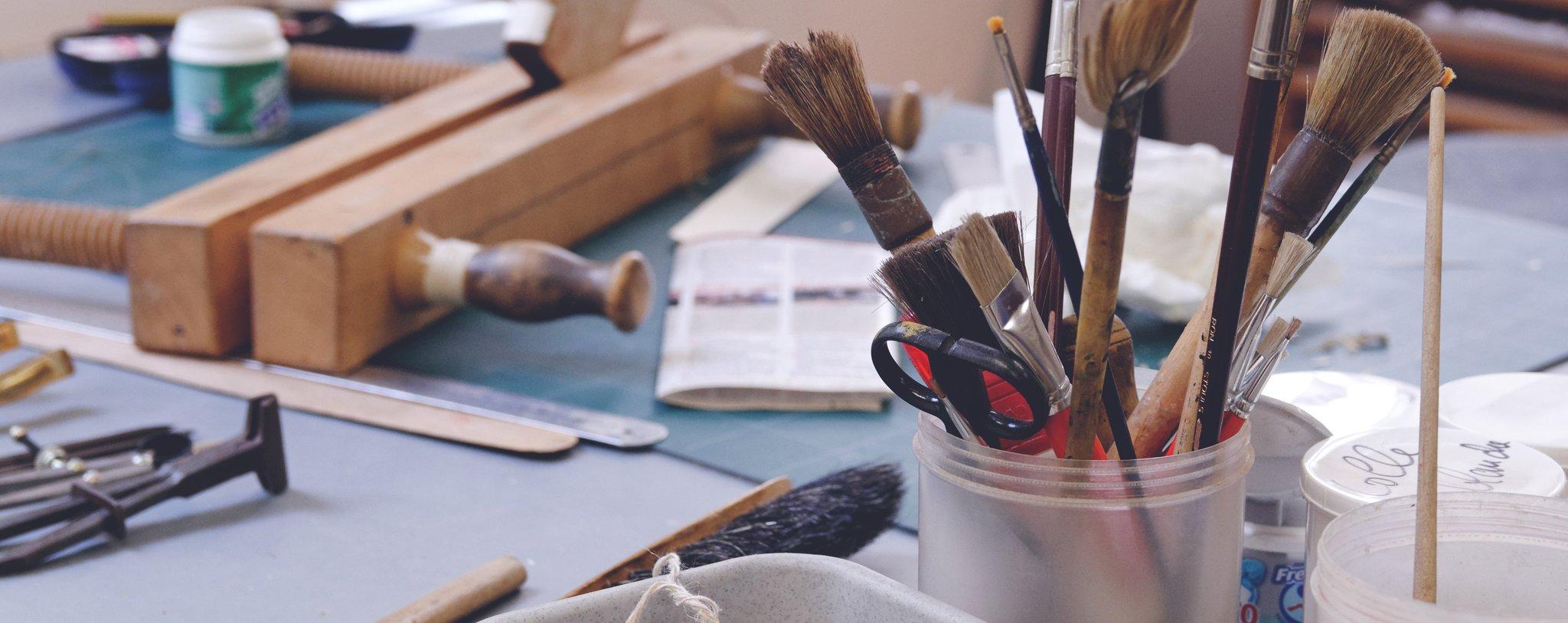 Na stole leżą metalowe cyrkle, gazeta, linijki, drewniane zaciski do ram obrazów, miotełka oraz kubeczek wktórym są pędzle ipędzelki. Obok stoja plastikowe, okrągłe pudełka.