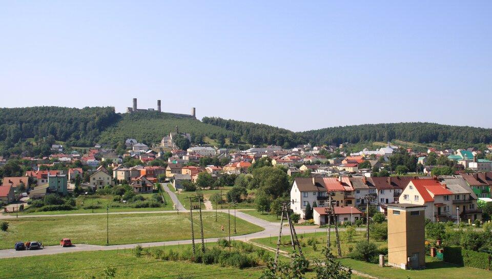Na zdjęciu zabudowania miejskie, wtle wzgórze zruinami zamku.