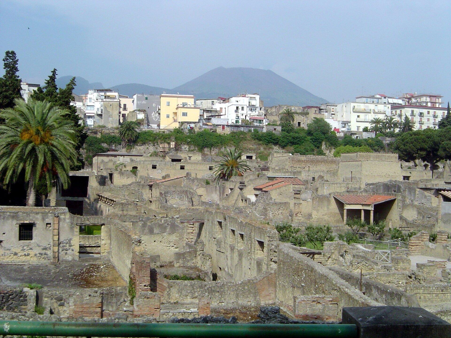 Na zdjęciu na pierwszym planie ruiny zabudowań, wtle dzisiejsze zabudowania, dalej góry.