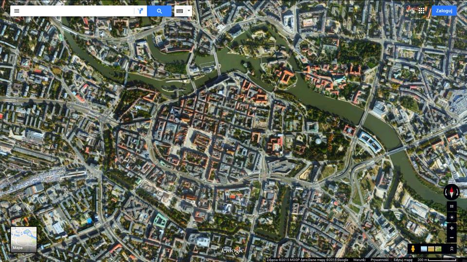 Fotografia druga przedstawia lotnicze zdjęcie centrum Wrocławia. Widoczny układ ulic izabudowy. Widać czerwone iszare dachy. Zprawego dolnego rogu do lewego górnego rogu wije się rzeka Odra. Od wschodu, południa izachodu fosa otacza ścisłe centrum miasta, aod północy Odra.