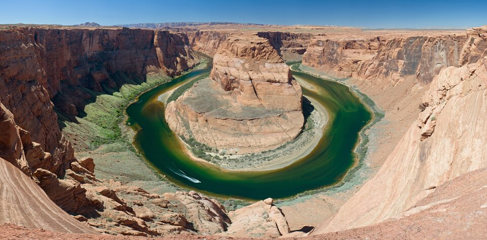 Na zdjęciu rzeka wdnie doliny obardzo stromych zboczach, płynąca dookoła skalistego ostańca.