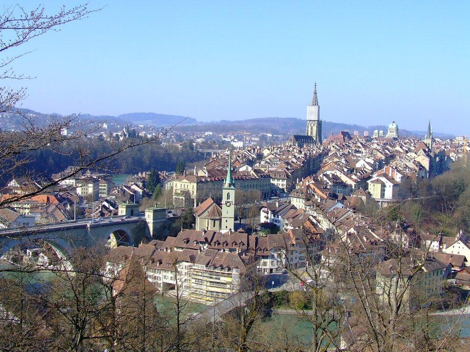 Na zdjęciu zwarta zabudowa miejska, czerwone spadziste dachy, kilka wież. Na pierwszym planie rzeka, kamienny most. Wtle łagodne góry.