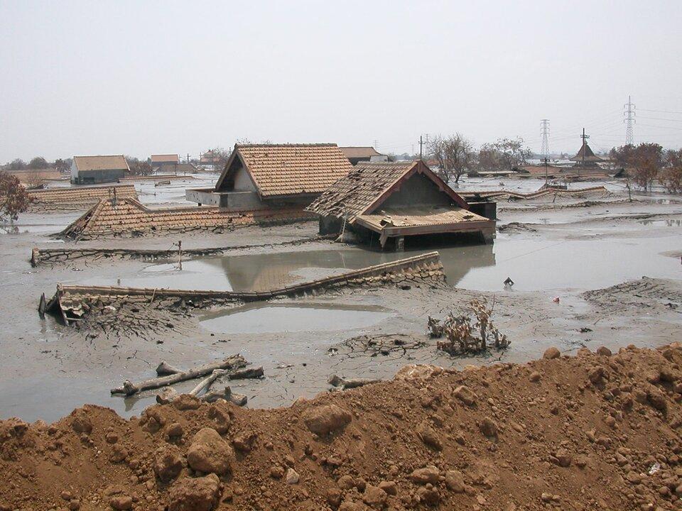 Na zdjęciu zabudowania mieszkalne pokryte po dachy warstwą mokrego błota.