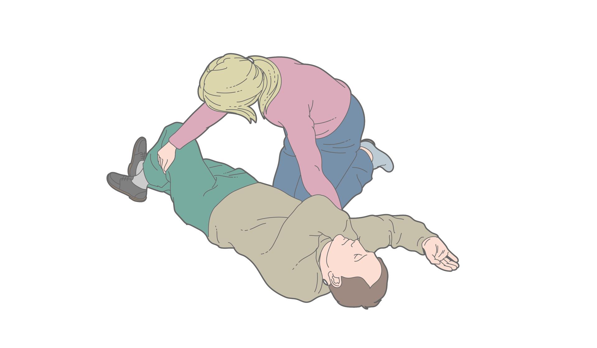 Poszkodowany mężczyzna leży nadal na plecach. Prawa ręka zgięta włokciu pod kątem prostym. Dłoń skierowana do góry. Lewa ręka ułożona wpoprzek klatki piersiowej. Lewa dłoń umieszczona pod prawym policzkiem poszkodowanego. Kobieta podciąga lewą nogę poszkodowanego wgórę tak aby nastąpiło zgięcie wkolanie. Stopa lewej nogi nadal na podłożu. Prawa noga wyprostowana na podłożu.