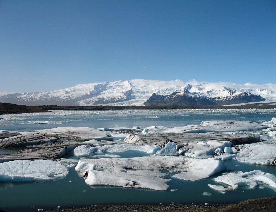 Na zdjęciu jezioro pokryte lodem, kawałki kry pływają po powierzchni. Wtle ośnieżone góry.
