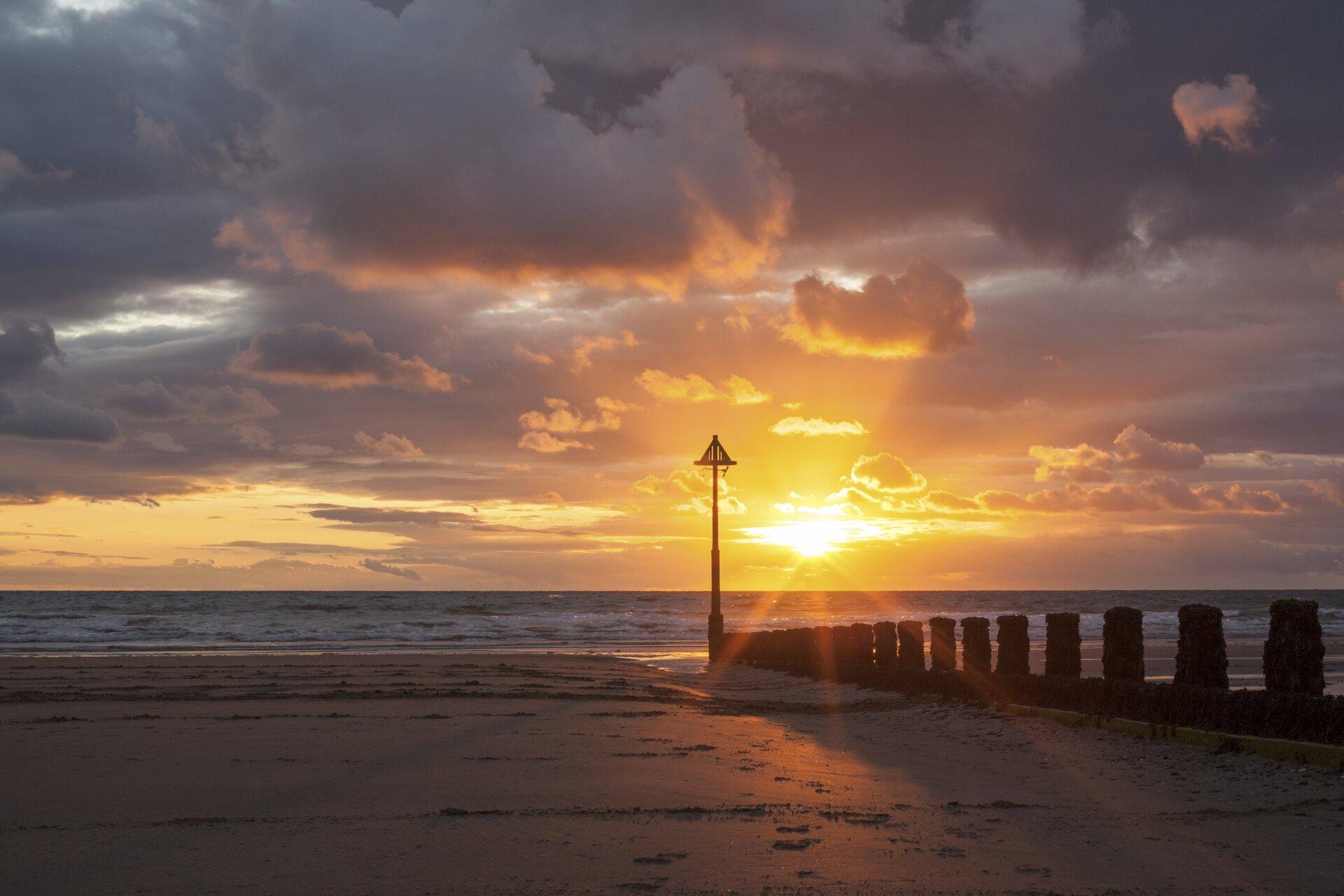 Fotografia przedstawia zachód Słońca nad brzebiem morza. Dolną część kadru zajmuje plaża imorze ukazane wciepłej kolorystyce zdługimi cieniami. Środkowa igórna część kadru to niebo ichmury. Słońce znajduje się wpołowie wysokości kadru, przesunięte nieco na prawo. Środkową część kadru zajmuje wysoki słup wbity wpiasek od którego wprawo, wkierunku pierwszego planu ciągną się paliki falochronu. Na piasku ślady ludzkich stóp.