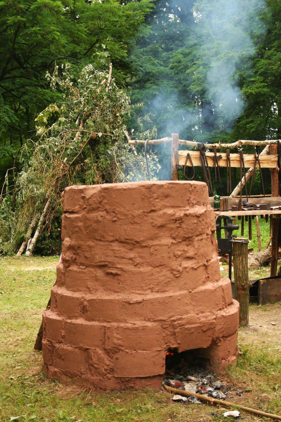 Zdjęcie przedstawia zrekonstruowaną dymarkę, czyli dawny piec hutniczy zcegieł igliny, wktórym wytapiane było żelazo zich rud. Wdolnej części dymarki widoczny jest otwór wktórym umieszczano węgiel drzewny iprzez który przedostawało się powietrze niezbędne do podtrzymania ognia.