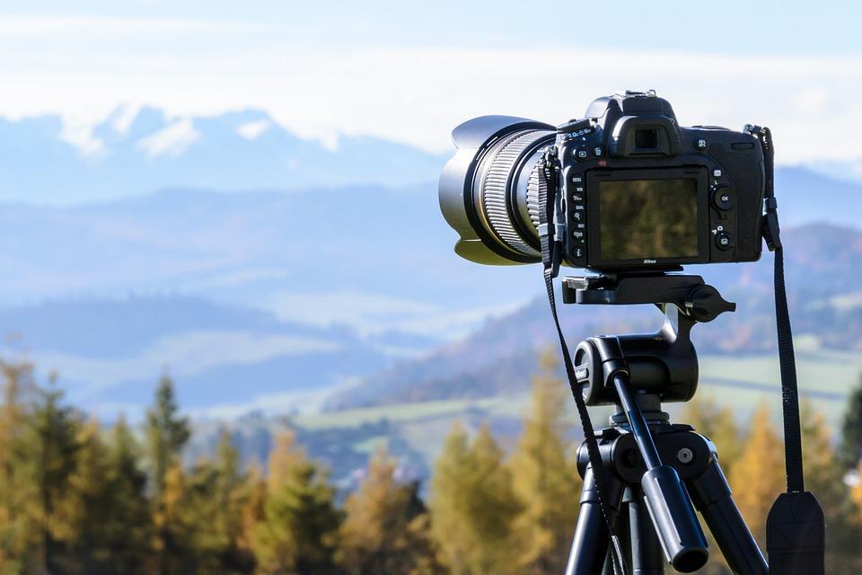 Zdjęcie przedstawia aparat umieszczony na statywie skierowany wstronę widoku na góry.