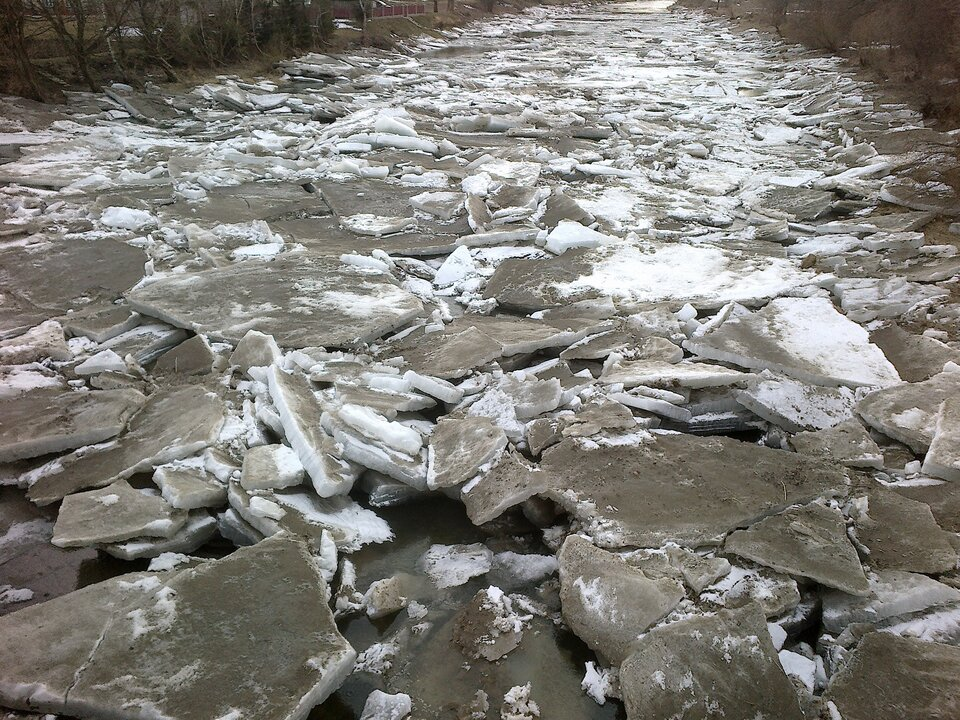 Na zdjęciu kawałki połamanego, brudnego lodu zapełniającego całe koryto rzeki.