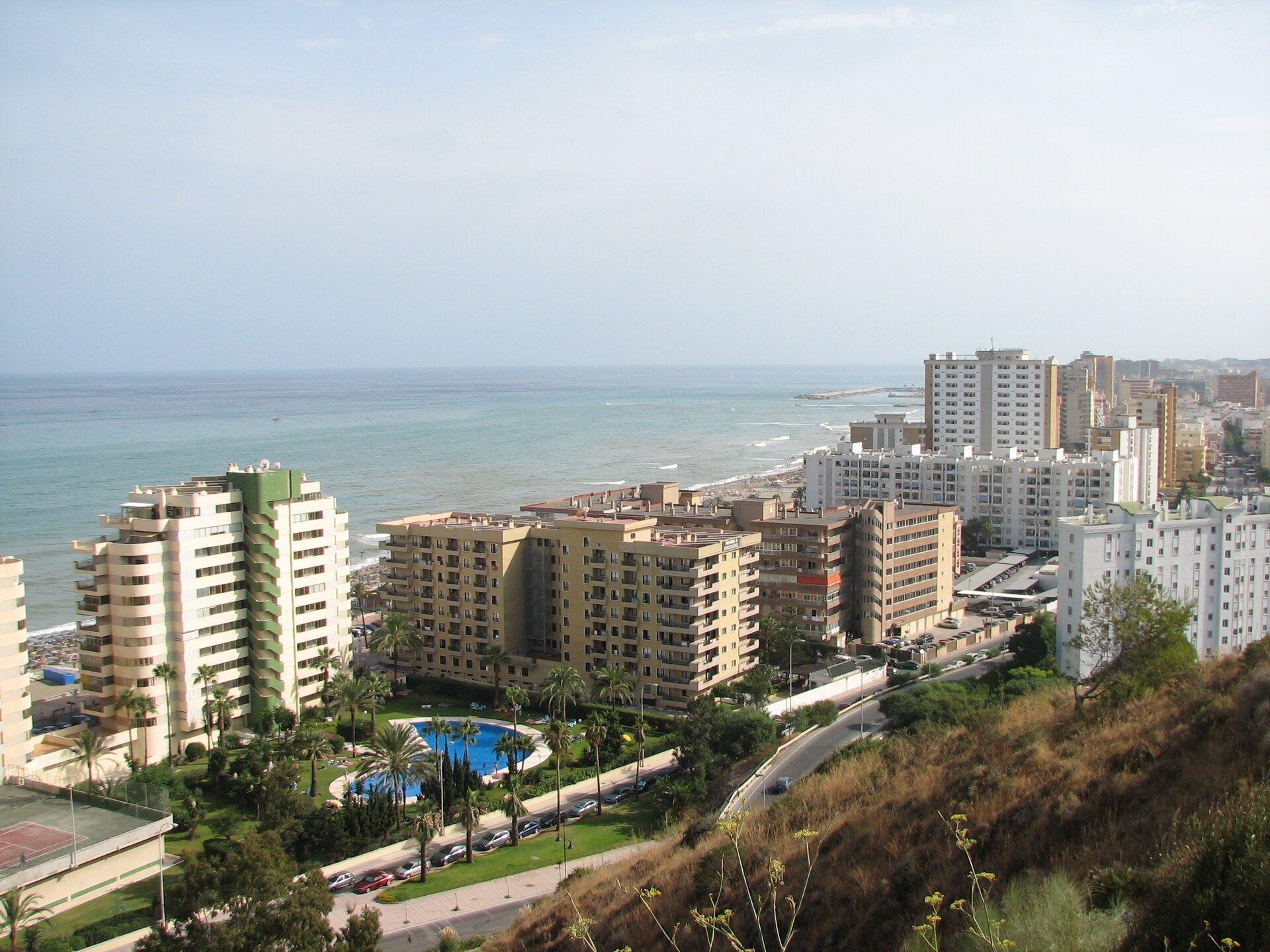 Na zdjęciu wysokie bloki przy brzegu morza. Pomiędzy budynkami bogata roślinność, basen.