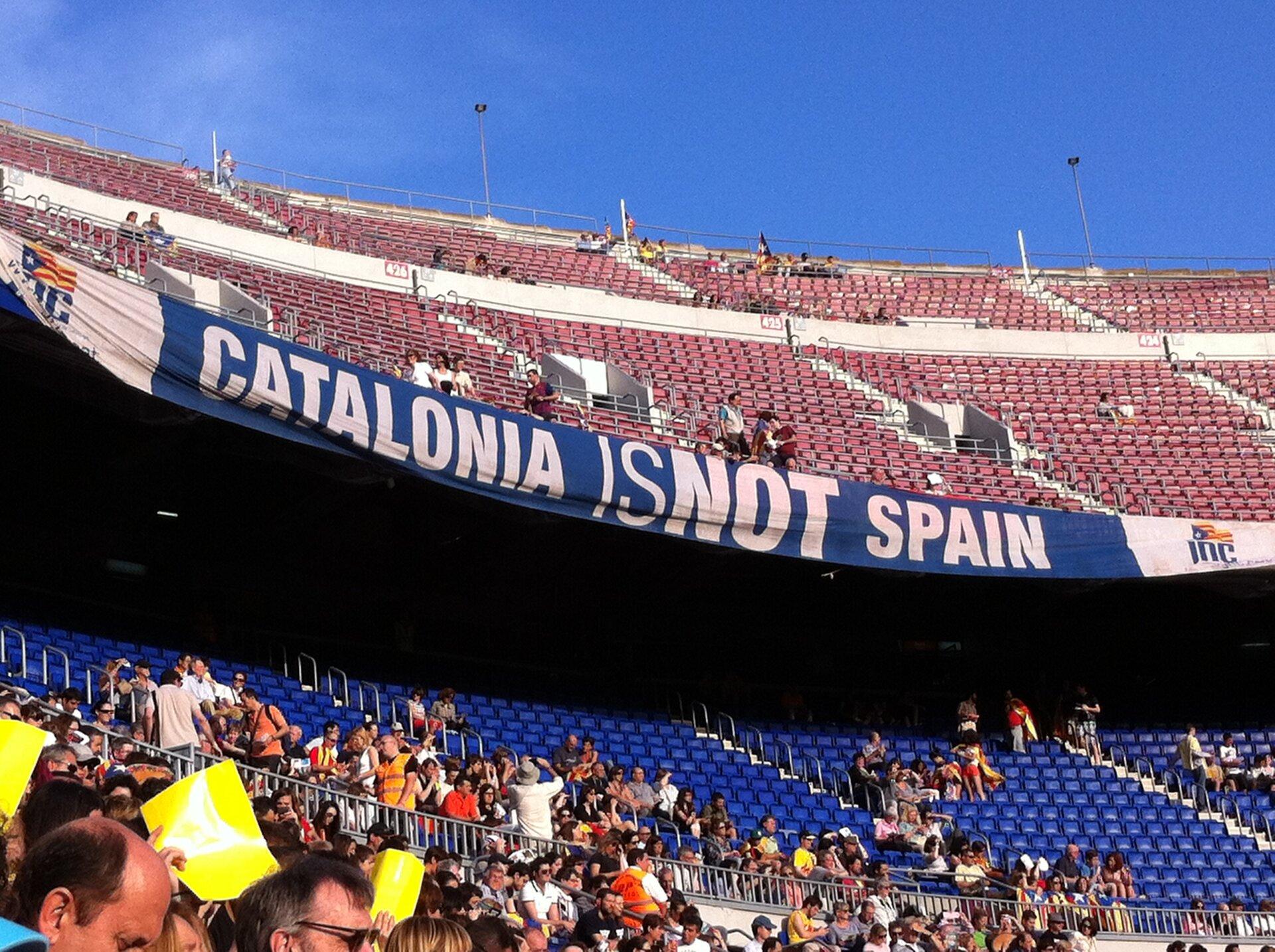 """Zdjęcie przedstawia duży stadion sportowy, częściowo wypełniony ludźmi. Na wyższej ztrybun wisi transparent znapisem """"Katalonia nie należy do Hiszpanii""""."""