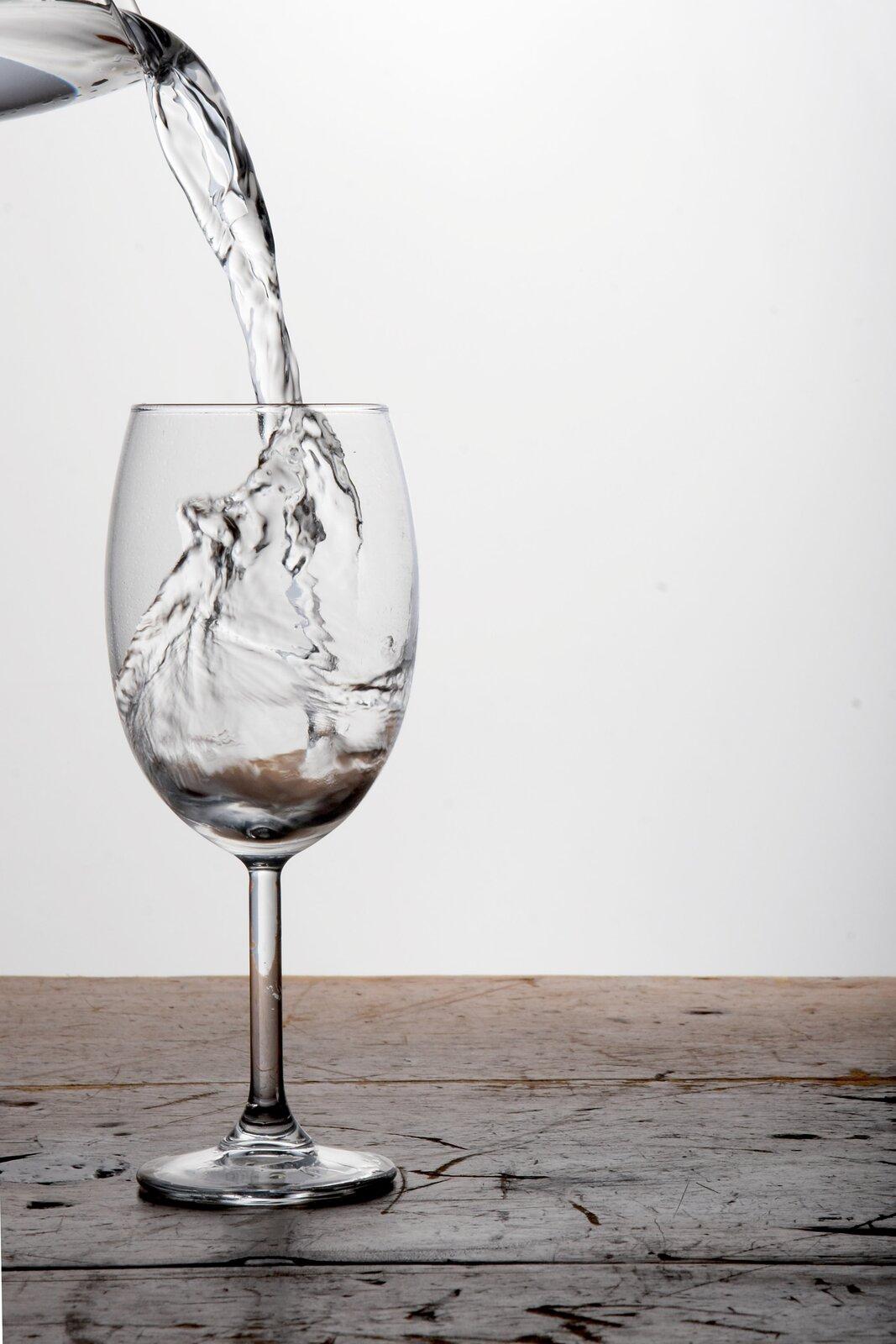Zdjęcie przedstawia czynność polegającą na nalewaniu wody do kieliszka. Tło jasne, kieliszek stoi na drewnianym stole. Kieliszek szklany, bezbarwny na wysokiej nóżce. Wlewym górnym rogu widać fragment dzbanka, zktórego nalewana jest woda.