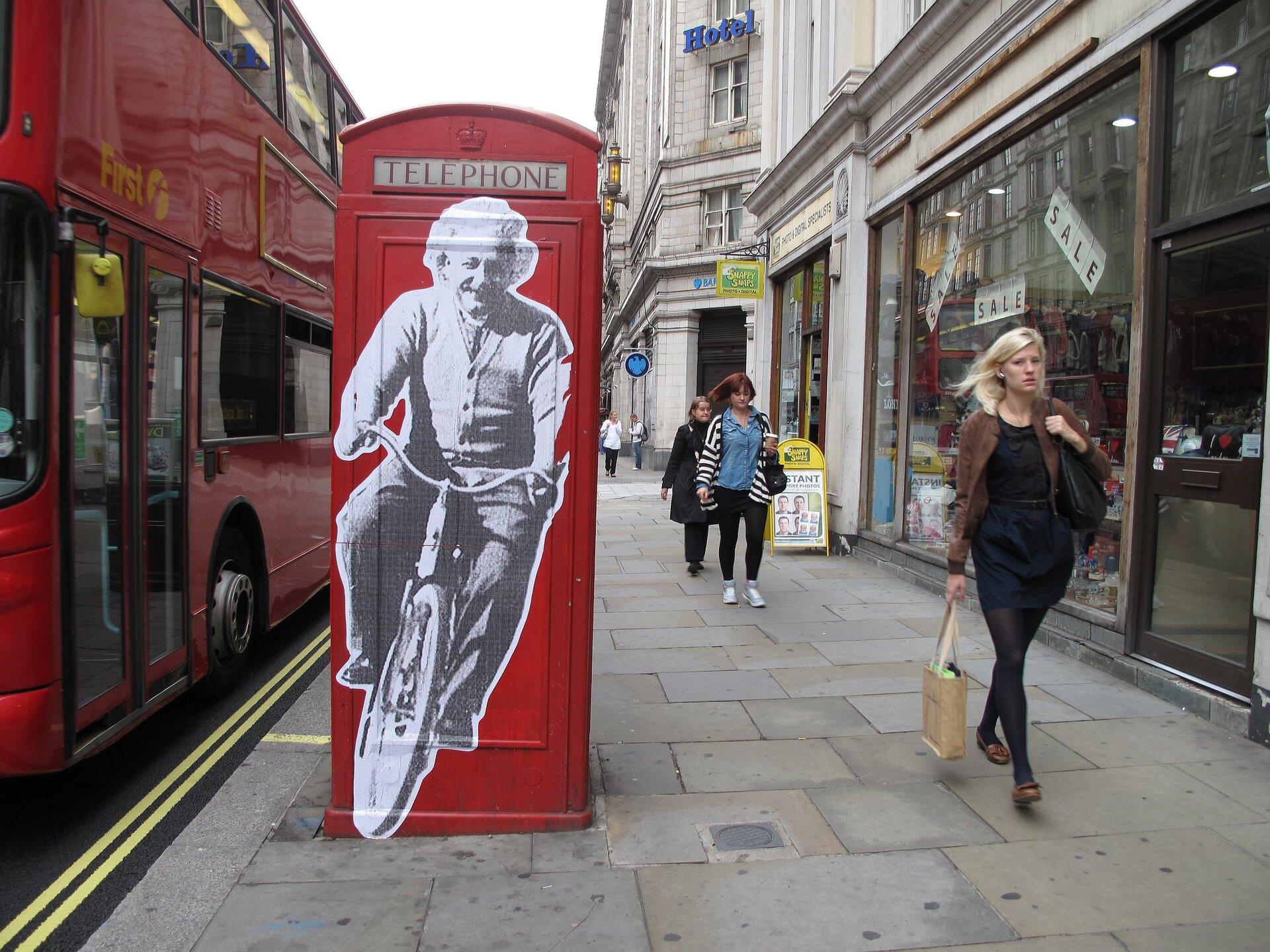 Zdjęcie przedstawia ulicę brytyjskiego miasta. Na pierwszym planie znajduje się typowa angielska czerwona budka telefoniczna, obok której przechodzą ludzie. Na budce wielka naklejka zwyciętą zfotografii sylwetką Alberta Einsteina jadącego na rowerze, uwiecznionego od frontu. Po lewej stronie budkę mija jadący ulicą czerwony dwupiętrowy autobus, po prawej widać ciąg starych budynków iwitryn sklepowych.