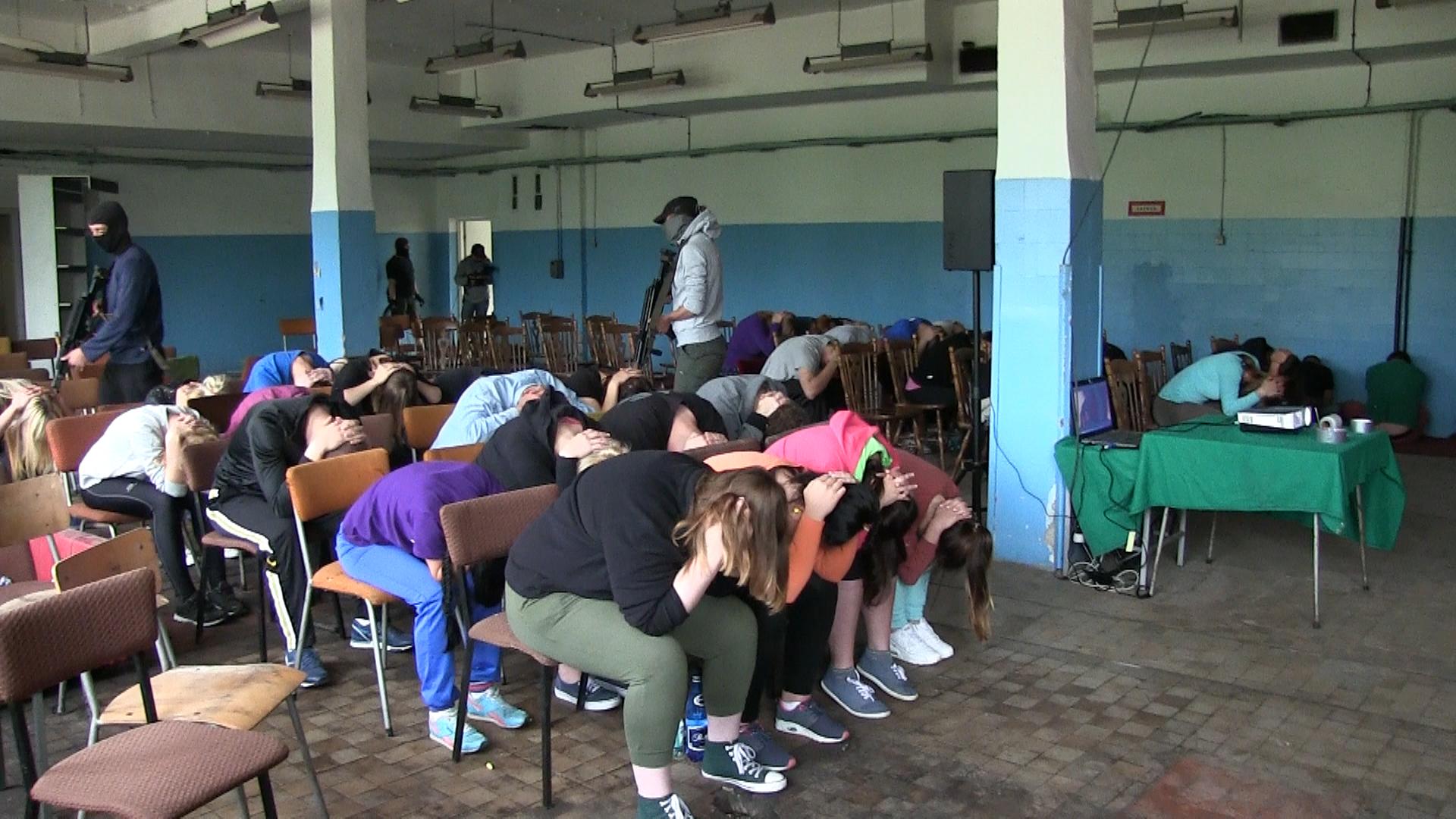 Zdjęcie przedstawia terrorystów wbudynku szkoły. Duża sala szkolna zkrzesłami ułożonymi wrzędach. Na krzesłach siedzą uczniowie. Wszyscy pochyleni do przodu. Ręce splecione nad głową. Czterej terroryści wczarnych kominiarkach chodzą między uczniami. Wrękach trzymają karabiny Wgłębi 2 terrorystów pilnuje wejścia do pomieszczenia zuczniami. Uczniowie są zakładnikami terrorystów.