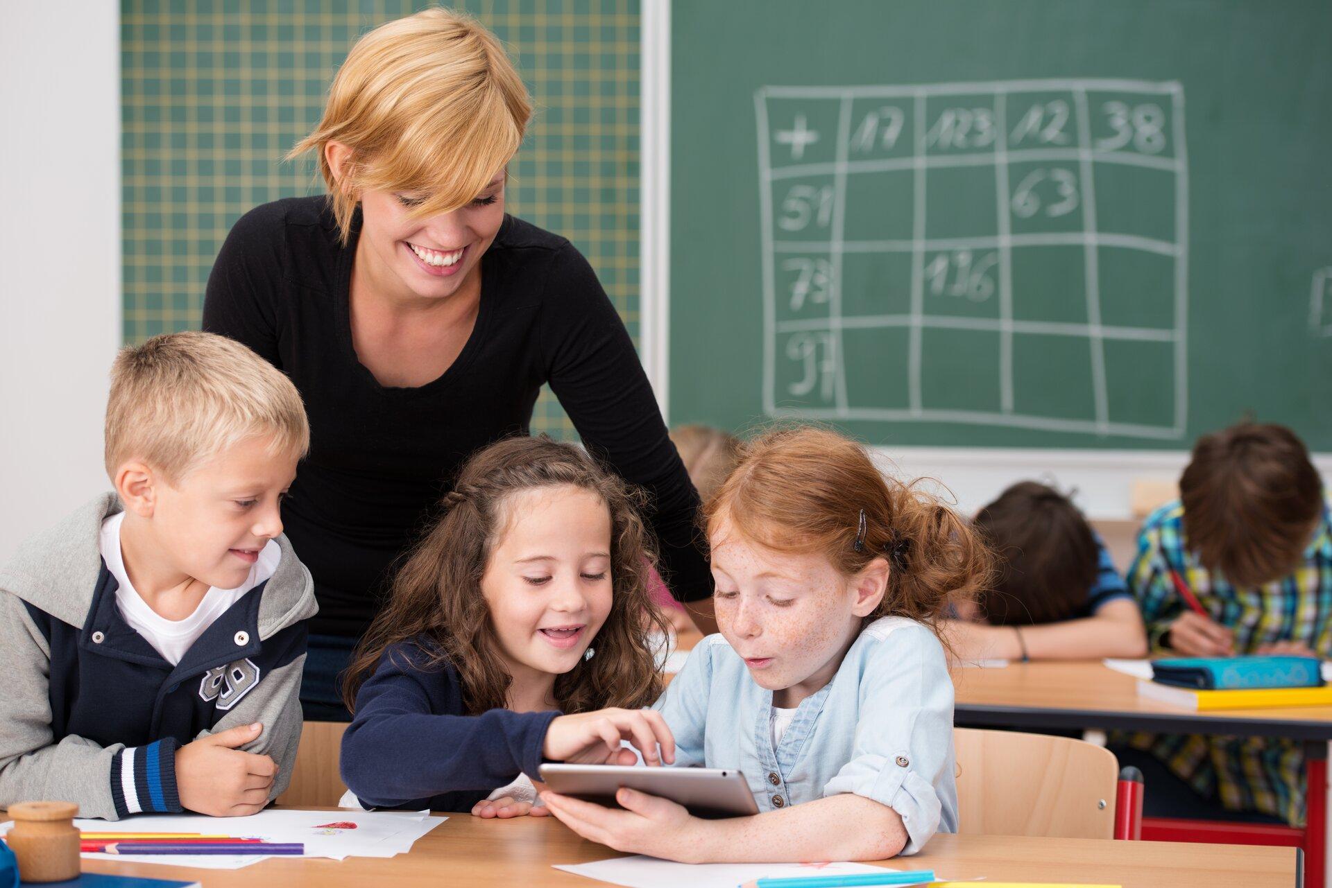 Ilustracja przedstawia lekcję wszkole. Ukazuje ona nauczycielkę idzieci korzystające ztabletu, który służy jako przedmiot dydaktyczny.