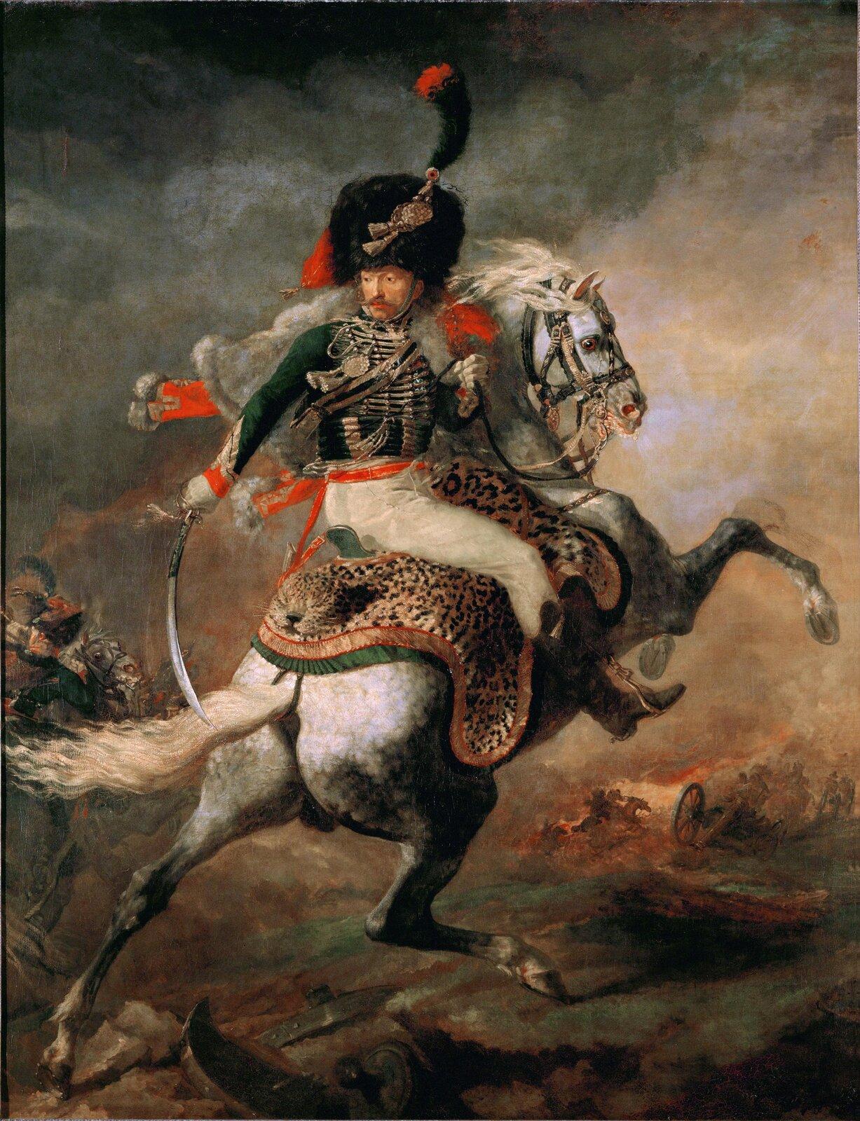 """Ilustracja przedstawia obraz Théodore'a Géricaulta """"Oficer szaserów"""". Obraz ukazuje oficera Gwardii napoleońskiej, Alexandra Dieudonné'a, który był przyjacielem artysty. Postać obraca się przyjmując dramatycznie skręcona pozę, wręku trzymam miecz, wyrażając gotowość do walki. Portret został wyeksponowany poprzez obniżoną linię horyzontu. Koń stający dęba ma zwróconą wprawo głowę. Wtle została przedstawiona scena bitwy, wzmocniona ciepłą kolorystyka, jednak nie jest to dzieło typowo batalistyczne – malarz zamieszcza jedynie jej fragment, anie panoramiczne ujęcie tematu, jak to miało miejsce wtypowych ujęciach tego typu. Géricault wzmacnia napięcie przez odważne wybory kolorów iróżnorodne efekty świetlne oraz ciemne, zachmurzone niebo."""