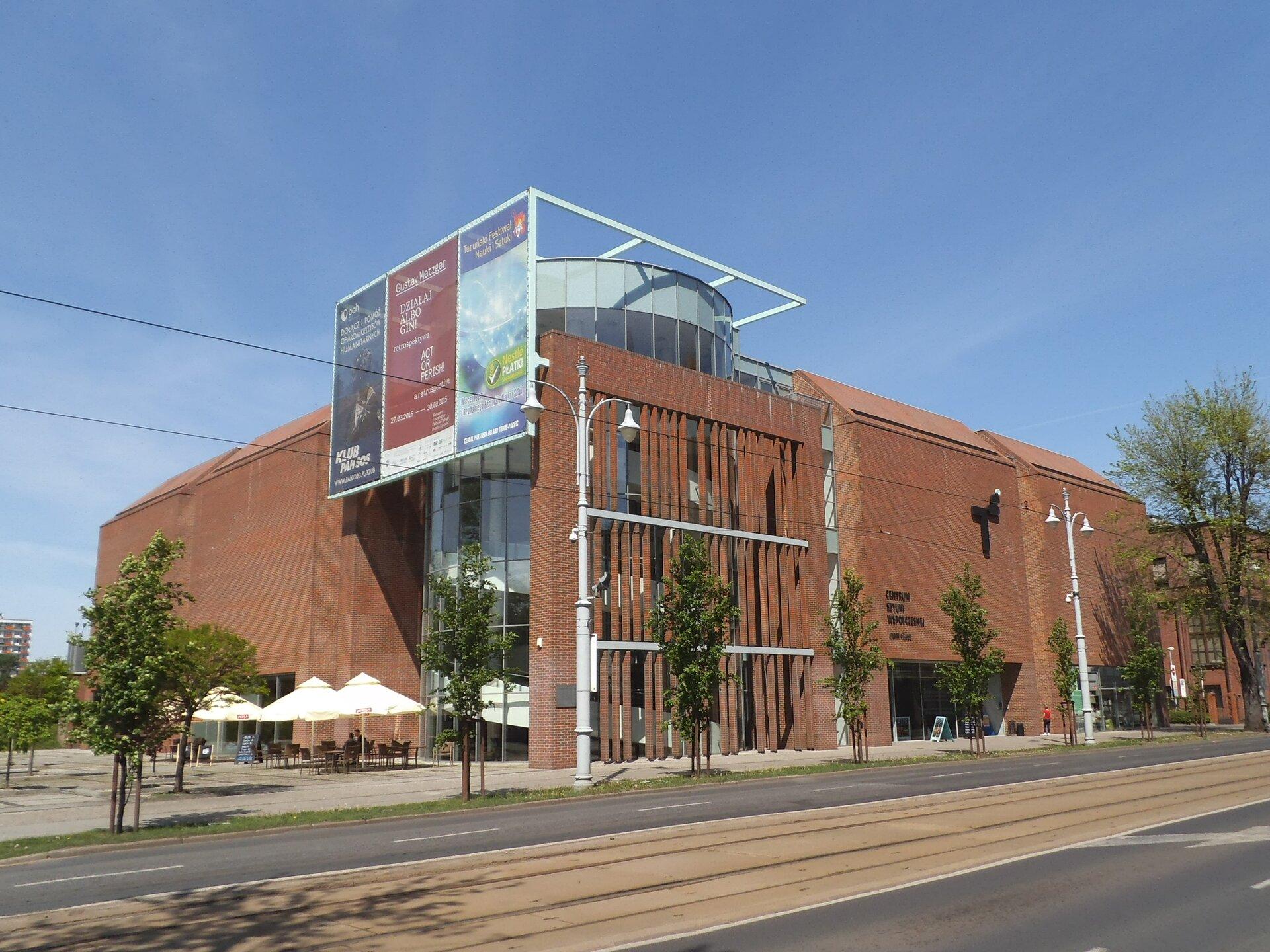 """Ilustracja przedstawia CSW """"Znaki Czasu"""" wToruniu - widok zzewnątrz. Budynek jest nowoczesny. Centralne wejście zbudowane zostało głównie ze szkła, nad którym znajdują się banery reklamowe. Budowla jest wkolorze brązowym, bez okien. Przed centrum sztuki znajdują ławki pod parasolami."""