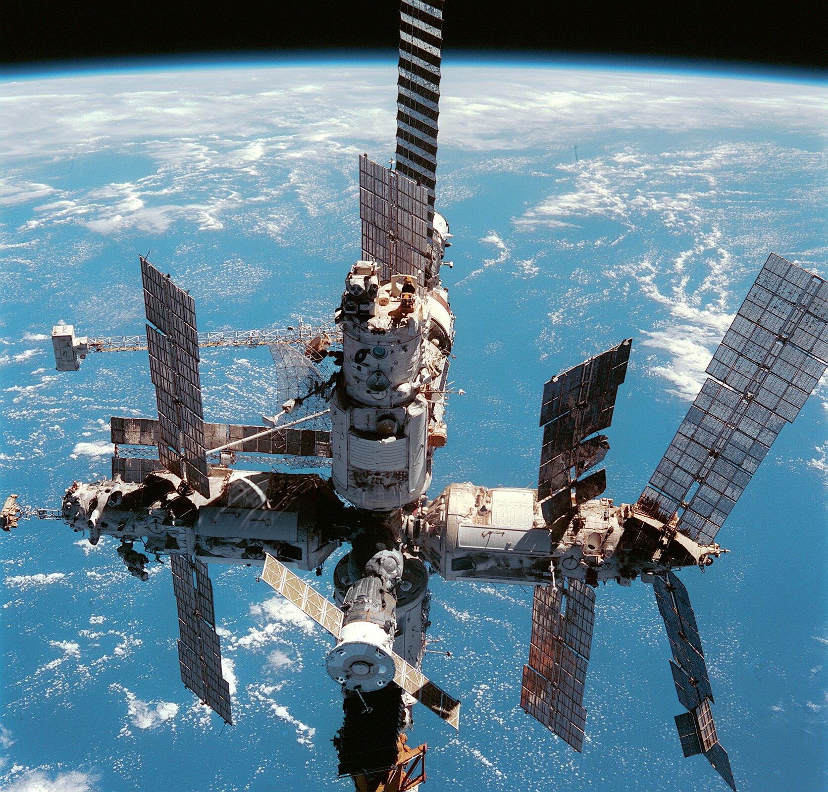 Zdjęcie przedstawia stację kosmiczną Mir na orbicie. Na pierwszym planie widoczna stacja kosmiczna, wtle kula ziemska.