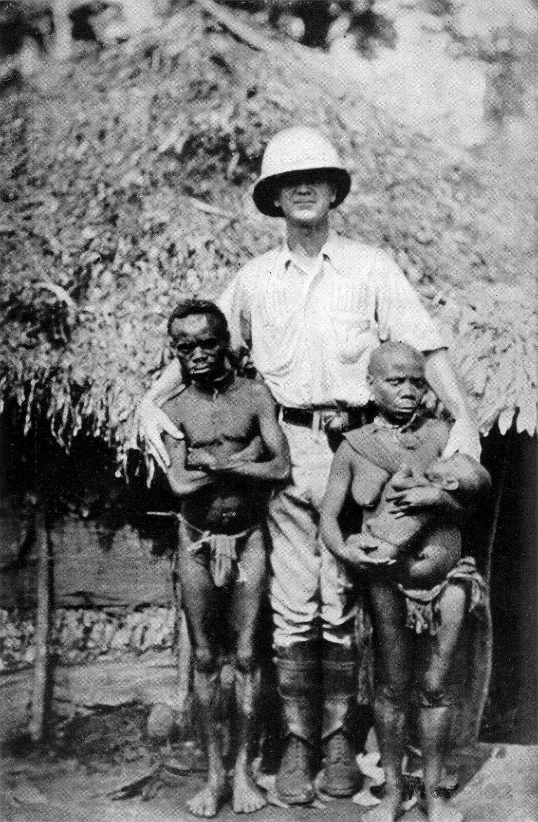 Badacz europejski wśród afrykańskich pigmejów Źródło: Badacz europejski wśród afrykańskich pigmejów, 1921, Collier's New Encyclopedia, Volume 1, domena publiczna.