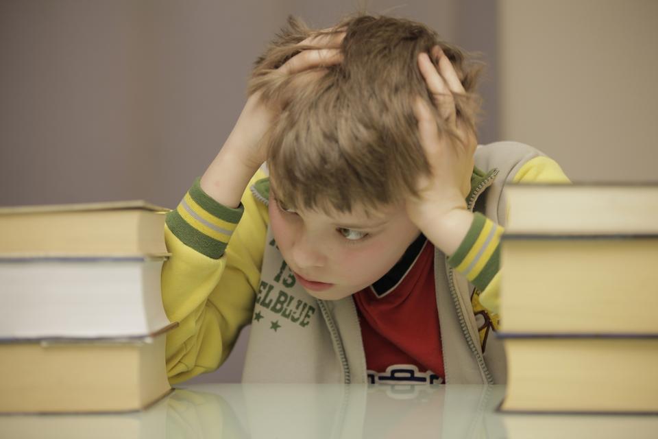 Fotografia przedstawia zestresowanego, zmartwionego chłopca. Chłopiec siedzi przy biurku, opiera na nim łokcie ipodpiera głowę dwiema rękami. Na biurku, po obu stronach siedzącego przy nim chłopca, znajdują się stosy książek.