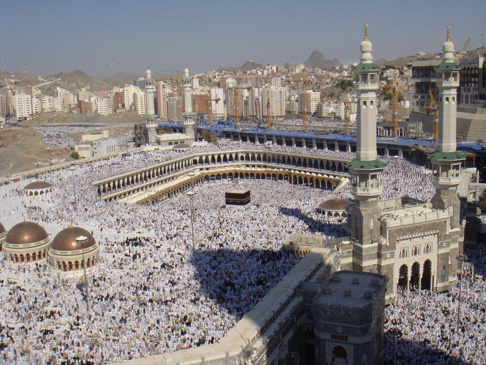 Na zdjęciu ogromny meczet pełen wiernych. Pośrodku prostokątna, czarna kamienna budowla (Kaaba). Po bokach minarety. Wtle wysokie budynki.