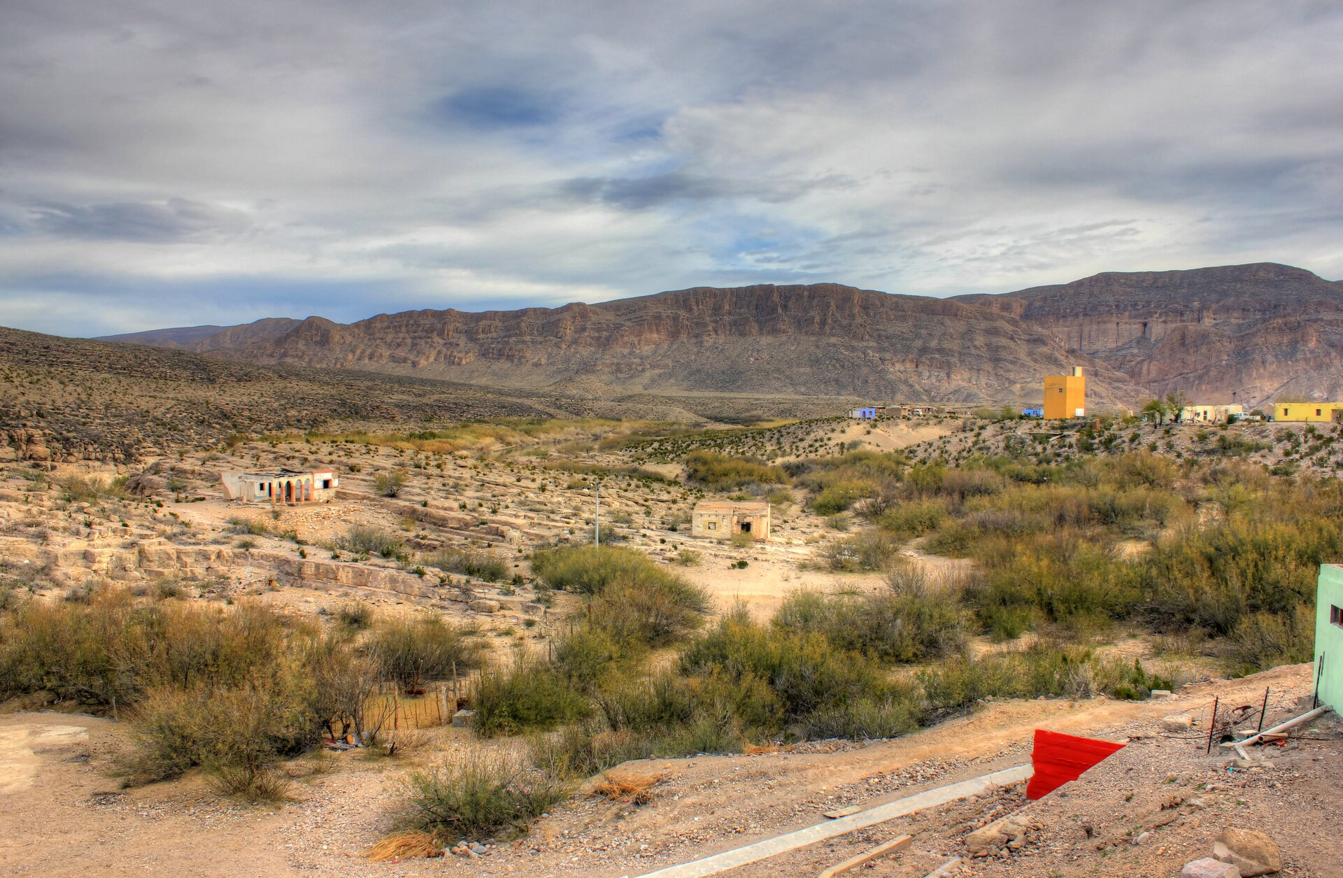 Na zdjęciu rozległe pofalowane tereny porośnięte rzadką roślinnością. Kilka pojedynczych zabudowań, wtle skaliste góry.