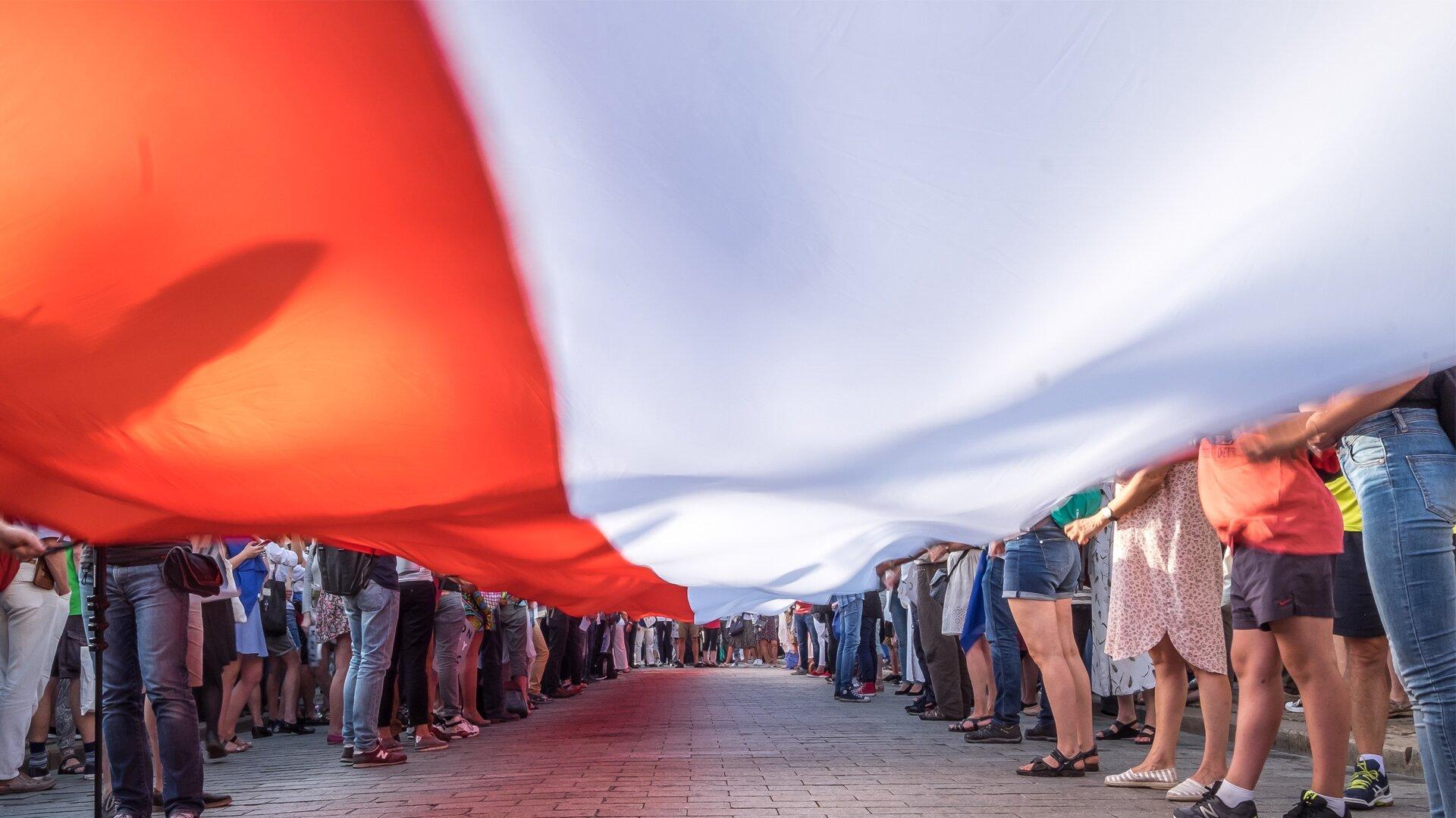 """Ilustracja przedstawia zdjęcie bardzo licznej grupy ludzi uczestniczących wpatriotycznej manifestacji. Duża grupa uczestników ustawionych wdwa szeregi ludzi ( kobiety imężczyźni ) trzyma rozciągniętą wpoziomie bardzo długą biało-czerwoną flagę Polski. Ujęcie jest bardzo ciekawe. Zdjęcie zrobione jest """" od spodu"""", zpoziomu powierzchni ulicy. Rozciągnięta flaga przesłania niebo isylwetki od pasa wgórę trzymających ją ludzi. Poza osobami trzymającymi flagę plac, na którym odbywa się manifestacja, wypełnia tłum innych uczestników manifestacji."""
