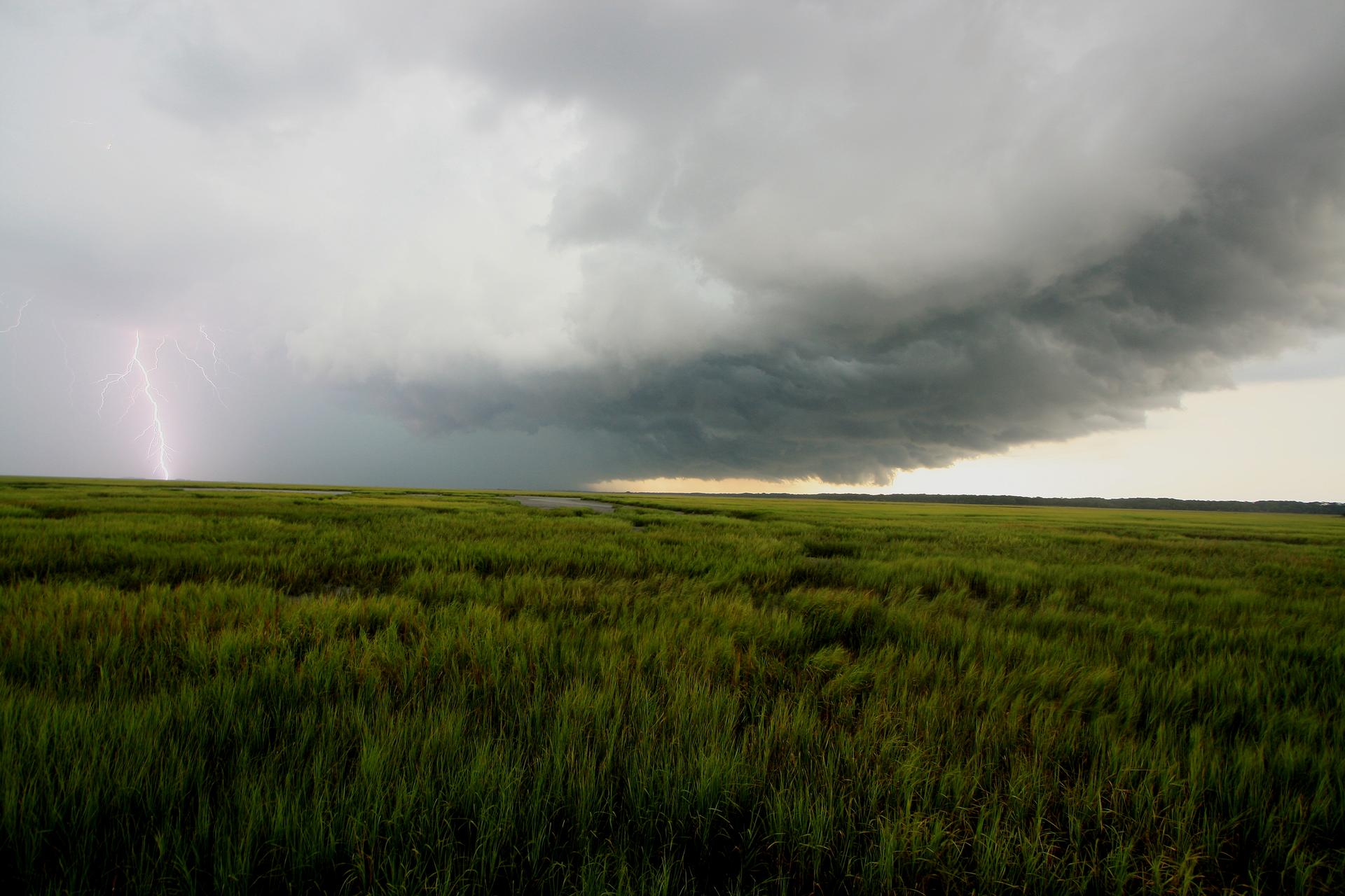 Zdjęcie ukazujące nadciągającą burzę iuderzenie pioruna. Na pierwszym planie widać, że jeszcze nie pada ijest spokój