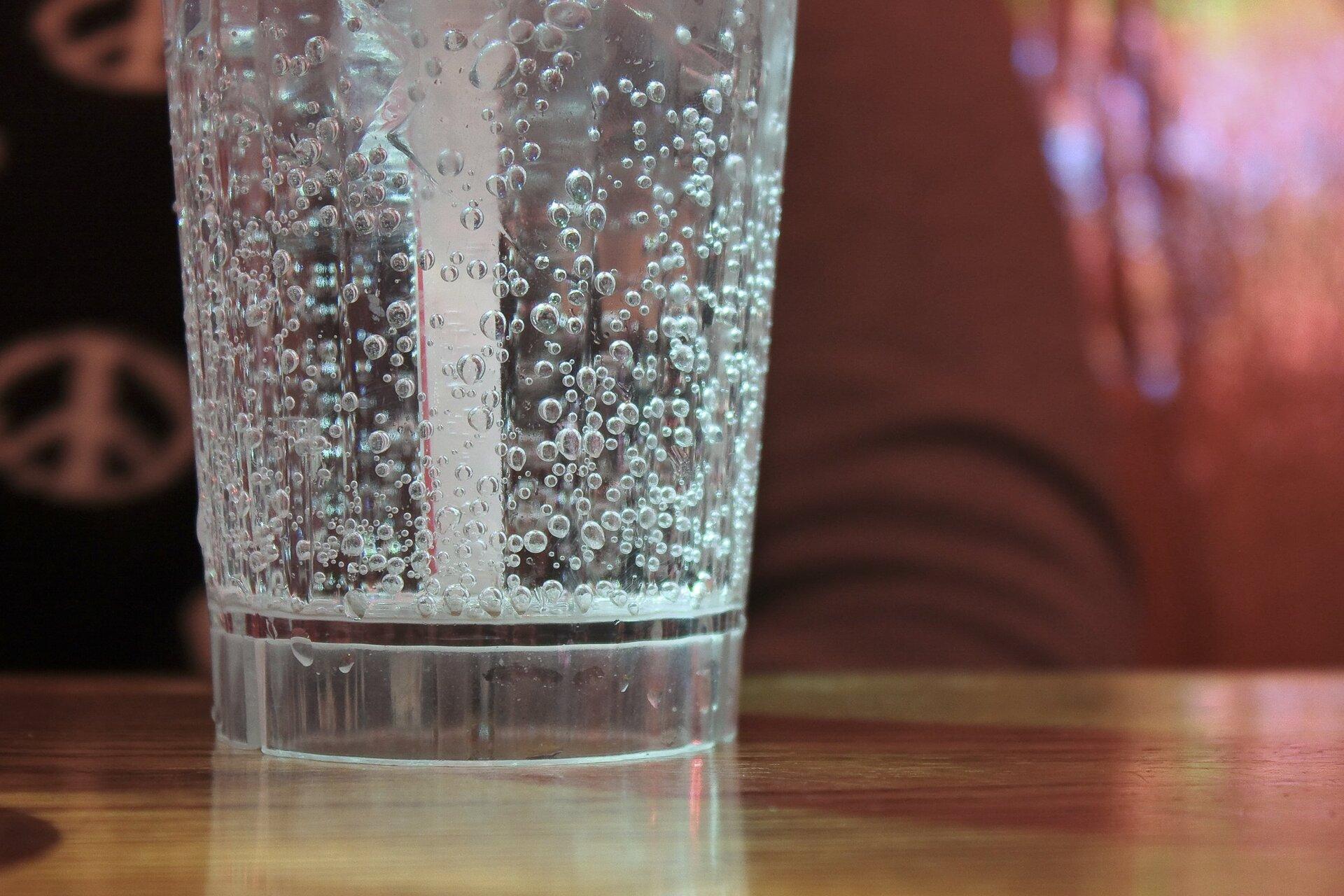 Zdjęcie przedstawia dolną połowę szklanki zwodą mineralną stojącą na blacie stołu. Wszklance oprócz wody znajduje się słomka oraz dużo wytrącanych bąbelków gazu przyległych do dna iwewnętrznych ścianek. Wtle fragment postaci ludzkiej ukazanej nieostro.
