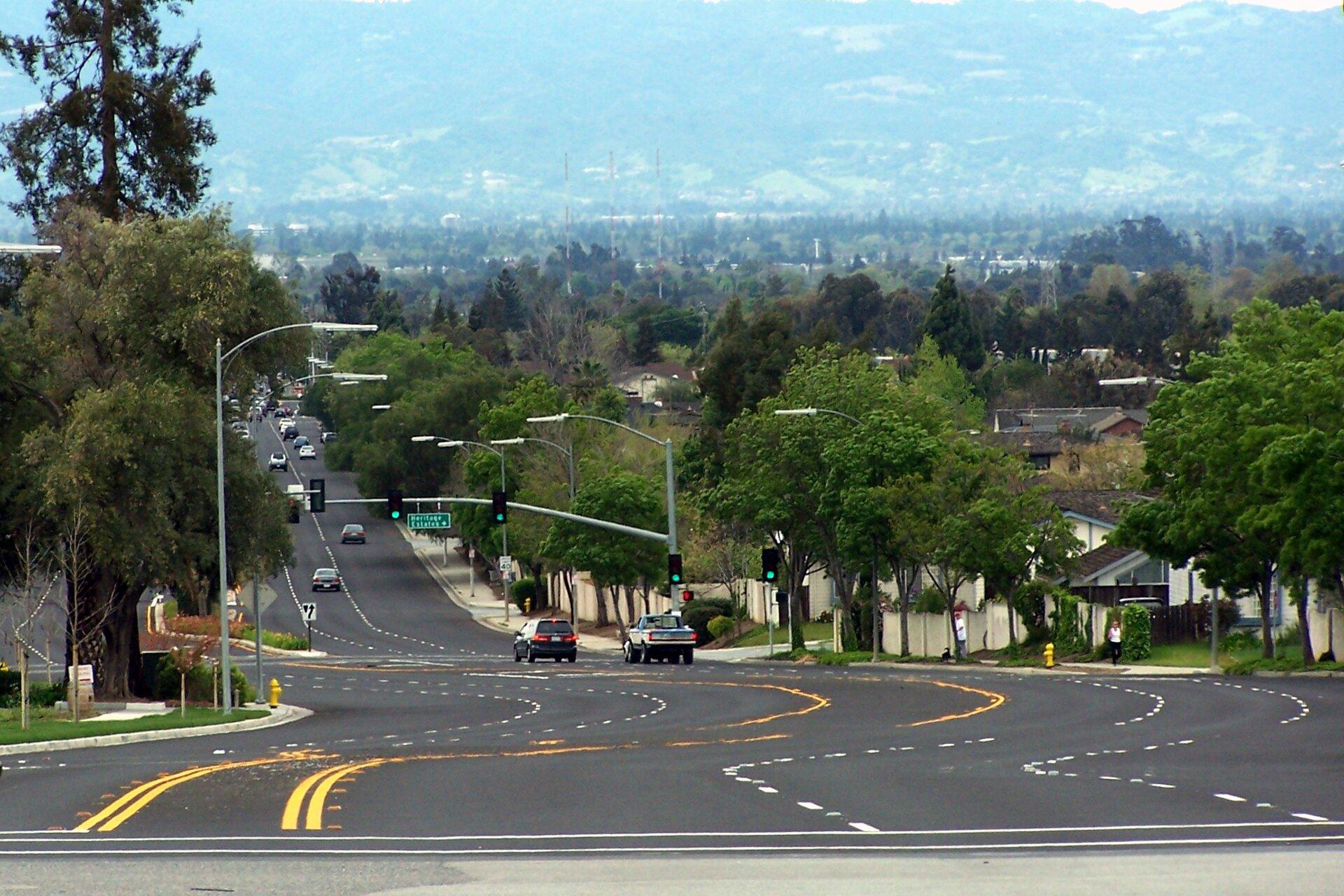 Na zdjęciu ulica wmieście, widok na rozległą dolinę porośniętą drzewami.