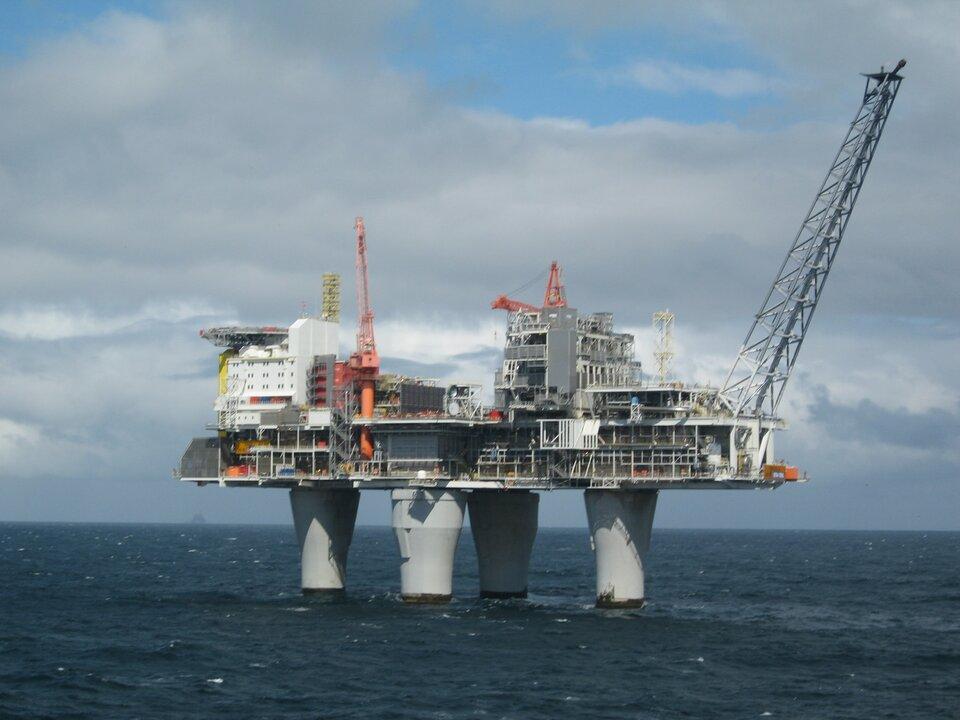 Na zdjęciu platforma wiertnicza na morzu. Cztery walcowe podstawy, platforma, na niej urządzenia, rury, wieże, dźwigi.