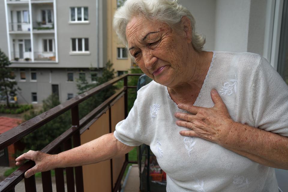 Kolorowe zdjęcie przedstawia starszą kobietę stojącą na balkonie. Kobieta jest zwrócona przodem do obserwatora, prawą ręką wspiera się ometalową balustradę balkonu, alewą dłoń przycisnęła do prawej strony klatki piersiowej. Ma przymknięte oczy. Twarz kobiety pokryta jest licznymi zmarszczkami. Jej usta są wąskie, zaciśnięte od bólu. Kobieta pochyla się lekko wlewo – wstronę balustrady.