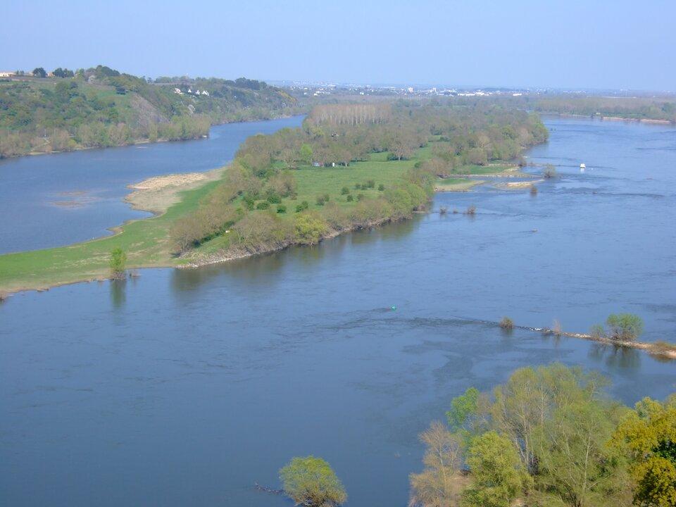 Na zdjęciu rozległa rzeka wterenie równinnym. Brzegi porośnięte lasem liściastym.