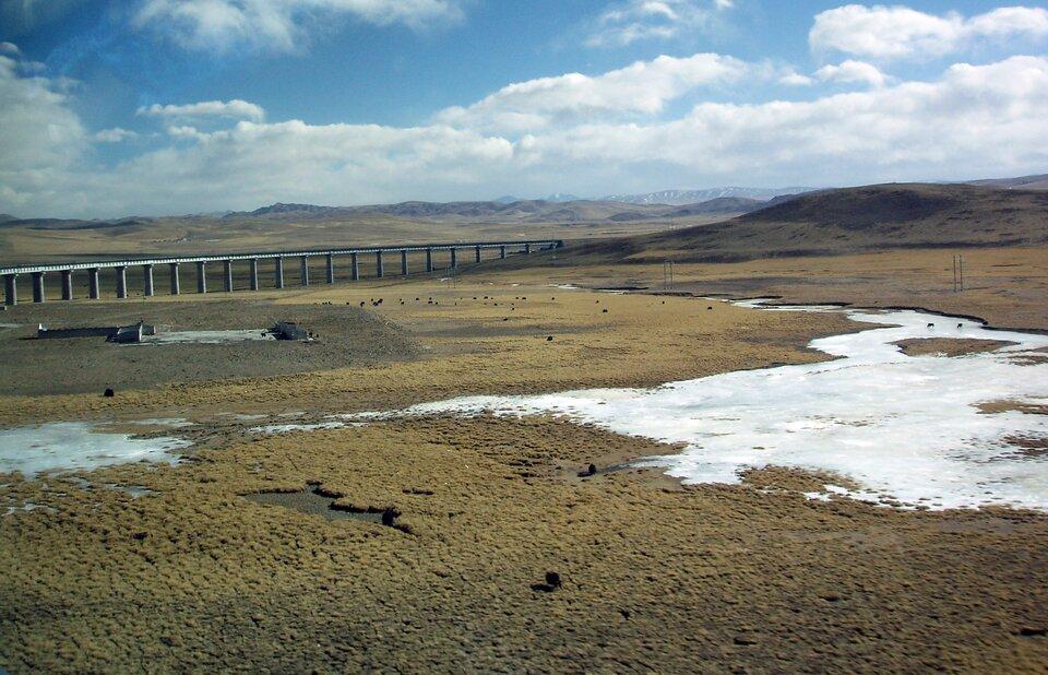 Na zdjęciu rozległe lekko pofałdowane obszary. Skąpa roślinność, zalegający śnieg. Most na filarach.