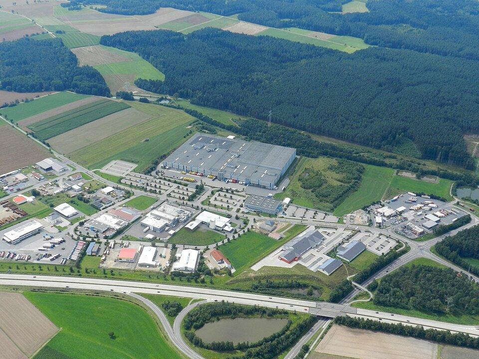 Na zdjęciu centrum logistyczne zlokalizowane na skrzyżowaniu ważnych arterii transportowych. Wyposażone jest wwęzeł transportowy, powierzchnie magazynowe, platformy przeładunkowe, obiekty biurowe, parkingi. Wtle rozległe tereny zielone. Las.