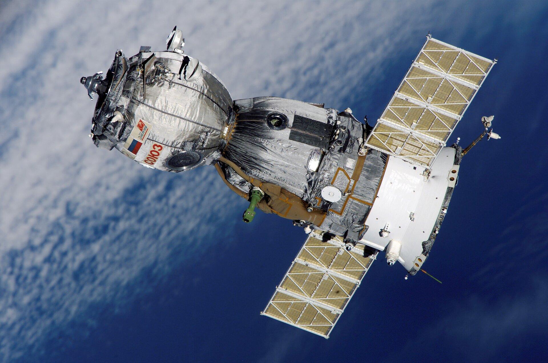 Fotografia prezentuje statek kosmiczny poruszający się wprzestrzeni okołoziemskiej. Satelita ma kształt cylindra zprzewężeniem wokolicach połowy jego długości. Po bokach satelity wystają prostokątne baterie słoneczne.