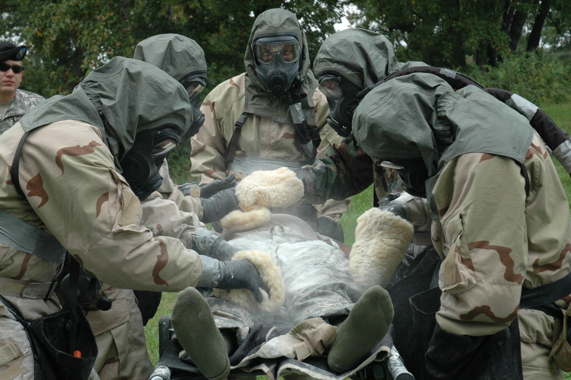 Zdjęcia przedstawia zabiegi sanitarne przeprowadzane przez grupę żołnierzy na człowieku leżącym na noszach. Na pierwszym planie nosze ipacjent na nich ułożony nogami do fotografa, na nogach ma skarpety, bez butów. Wokół niego grupa pięciu żołnierzy ubranych wkombinezony ochronne imaski. Wszyscy mają głowy okryte ciemnozielonymi kapturami oraz rękawice na rękach. Żołnierze usuwają mechanicznie niebezpieczne substancje zubrania osoby na noszach za pomocą specjalnych myjek przypominających gąbki kąpielowe. Wtle widoczna zieleń trawy, drzewa oraz obserwujący akcję oficer wmundurze polowym, bez stroju ochronnego.