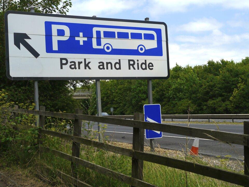 Na zdjęciu znak drogowy. Napis zaparkuj ipojedź. Litera pe iautobus. Wtle droga ilas.