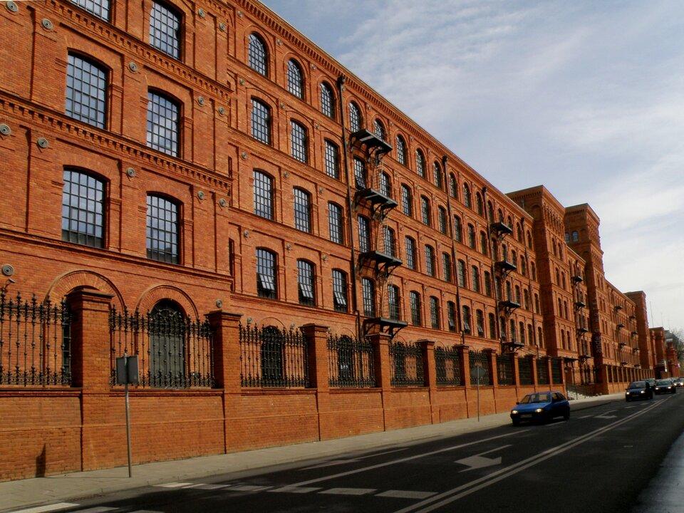 Na zdjeciu czteropiętrowy budynek fabryczny zczerwonej cegły otoczony wysokim płotem. Przed budynkiem dwupasmowa ulica, samochody.