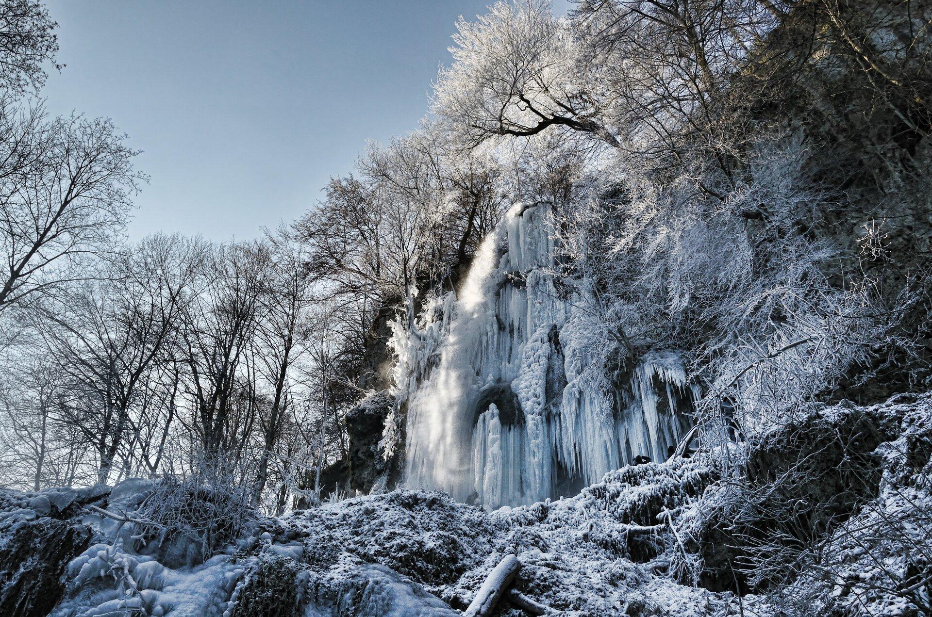 Zdjęcie przedstawia wodospad zimą uwieczniony od jego podstawy. Najbliższe okolice wodospadu oraz większa część jego powierzchni pokryte są lodem. Drzewa rosnące poniżej skalnej półki zktórej wypływa woda również są silnie oszronione. Pozostałe drzewa mają gałęzie nagie. Prawa idolna krawędź kadru zajęta przez ośnieżone skały. Wlewym górnym rogu kadru niebieskie bezchmurne niebo.