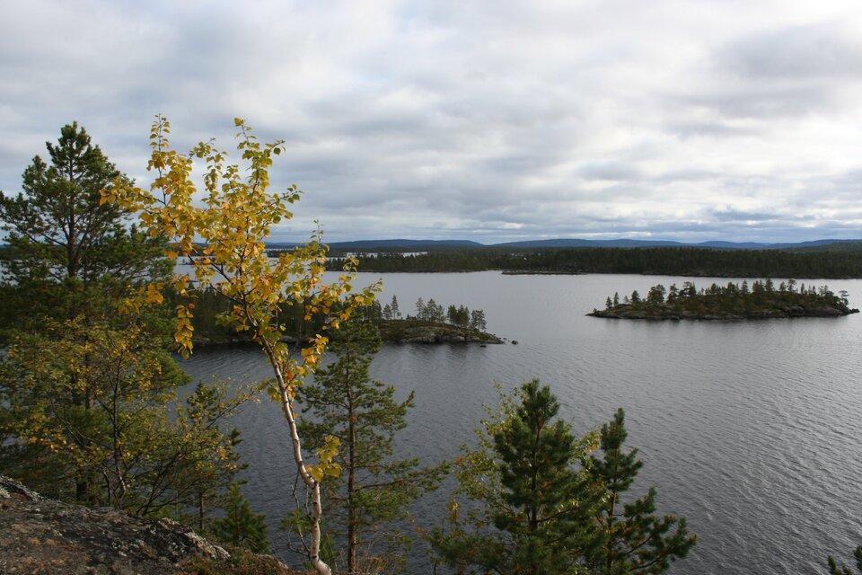 Na zdjęciu jezioro, małe wąskie wysepki porośnięte drzewami. Wtle pasmo górskie.