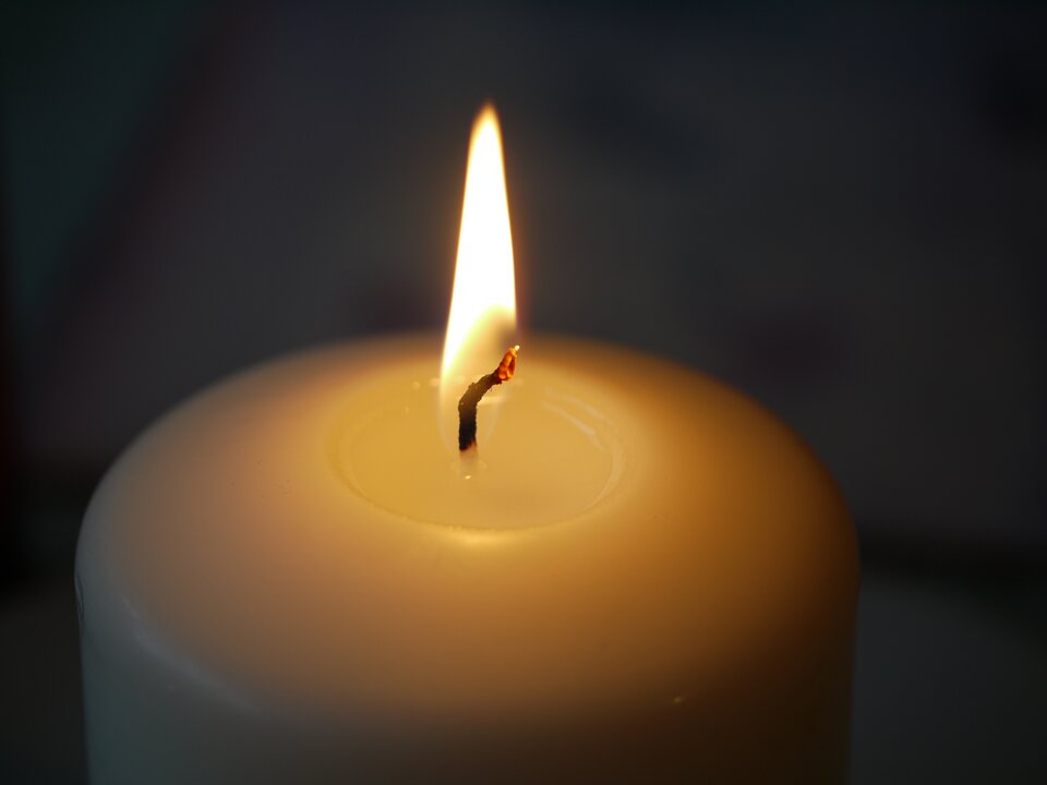 Zdjęcie przedstawia górną część świecy. Świeca ma średnicę około pięć centymetrów. Na szczycie świecy krótki knot. Knot jest zapalony. Koniec knota jest rozżarzony iczerwony. Dolna część knota jest czarna. Koniec knota wychodzący ze świecy jest biały. Cały knot od części czarnej do czerwonej jest wpłomieniu. Płomień ma kolor biały. Płomień ma kształt wydłużonego trójkąta. Tło zdjęcia czarne.