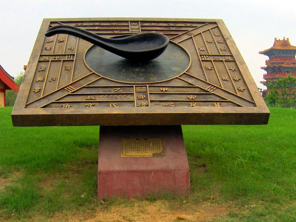 Fotografia prezentuje jeden zpierwszych kompasów skonstruowany wChinach. Kompas składa się zprostokątnej tarczy na środku, której przytwierdzono igłę wkształcie łyżki.